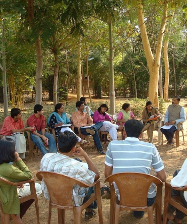 Group discussion in the camps of Nirman (cropped), by Abhijeet Safai, Public Domain via Wikimedia Commons