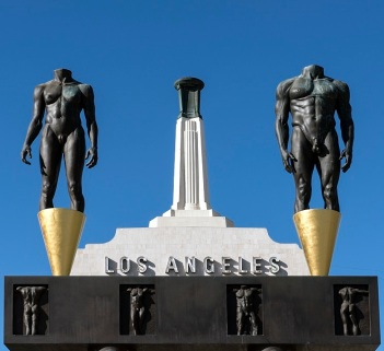 The Olympic Gateway arch and male and female statues at the entrance to the Los Angeles Memorial Coliseum, Los Angeles, California by Robert Graham, public domain via Library of Congress