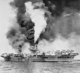 Kamikaze attack left HMS Formidable burning, 1945, by Royal Navy photographer aboard HMS Victorious (cropped), public domain via Wikimedia Commons