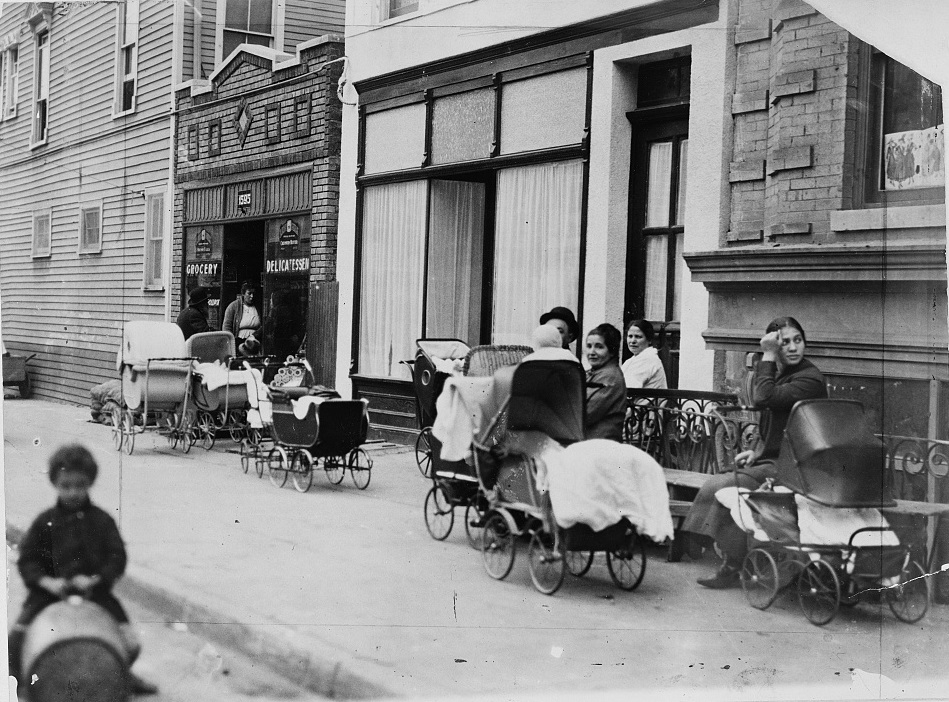 Photograph shows women and men sitting with baby carriages in front of the Sanger Clinic, LOC